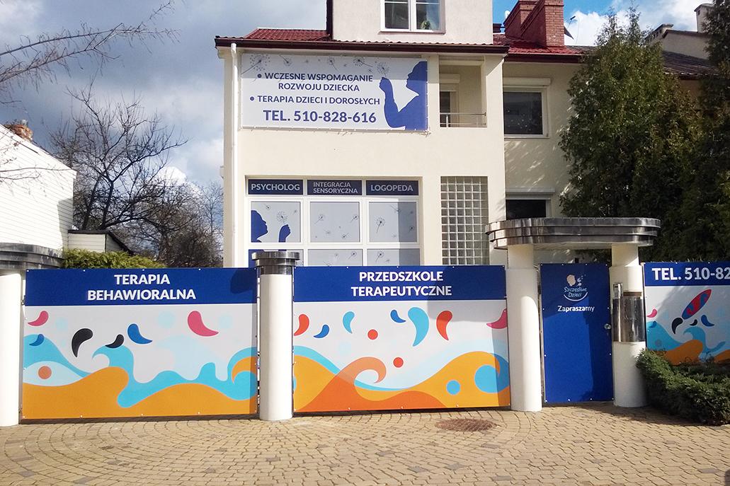 reklama zewnętrzna z grafiką na ogrodzeniu dla przedszkola Szczęśliwe Dzieci
